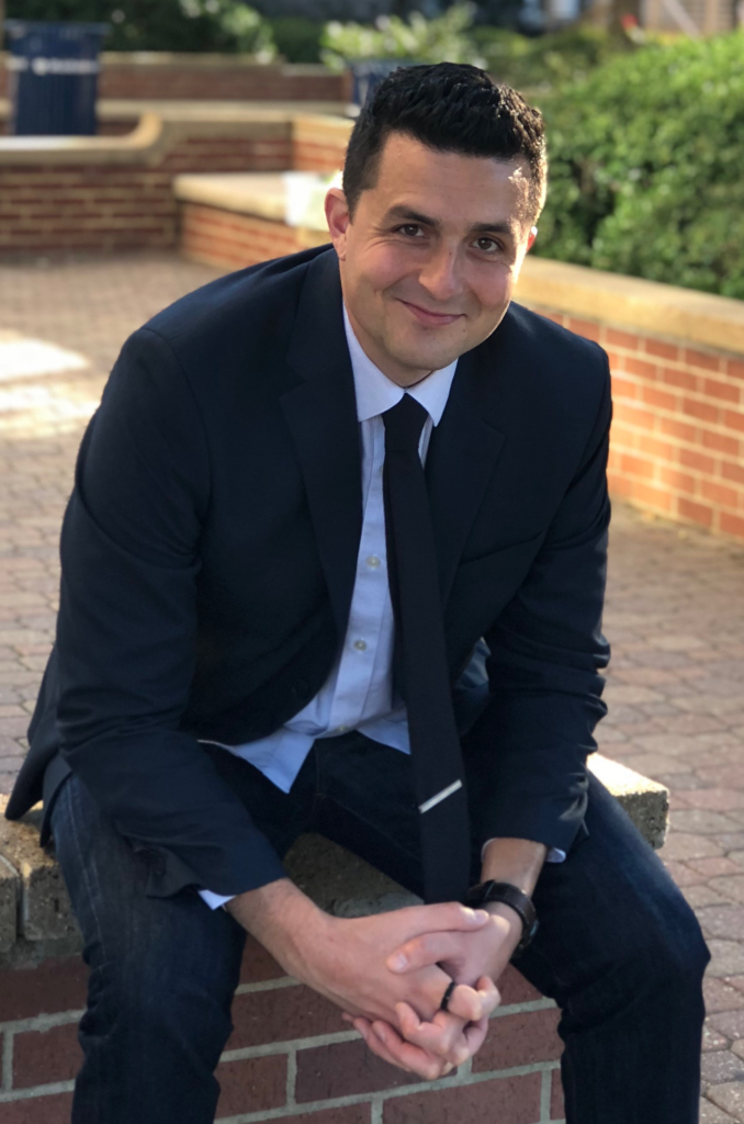 Photo of Dan Richards sitting in a brick bench on Old Dominion's campus. Sun is out, and a half smile is on Dan's face.
